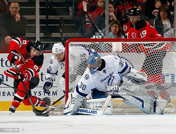 Goalie Dwayne Roloson of the Tampa Bay Lightning covers the net as Zach Parise of the New Jersey Devils circles the net to try to score on a backhand...
