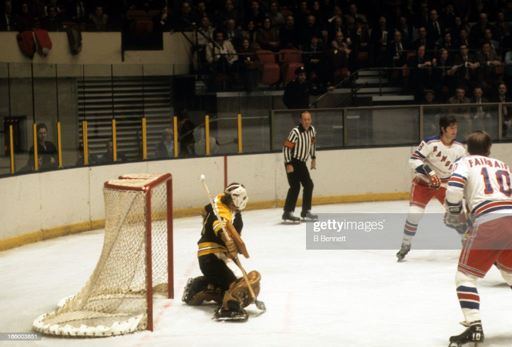 Goalie Eddie Johnston of the Boston Bruins defends the net as Steve Vickers and Bill Fairbairn of the New York Rangers look for a pass on October 18...