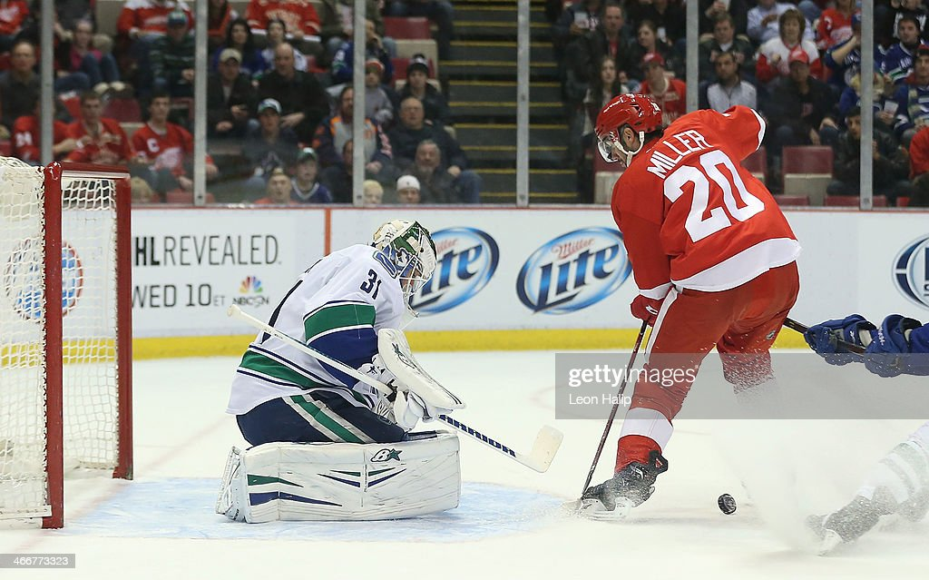 Goalie Eddie Lack #31 of the Vancouver Canucks defends the net as Drew Miller #20 of the Detroit Red Wings has the puck knocked away during the first period of the game at Joe Louis Arena on February 3, 2014 in Detroit, Michigan. The Red Wings defeated the Canucks 2-0.