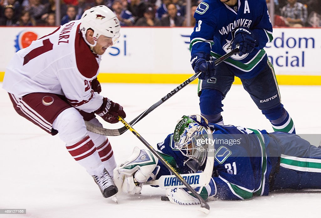Goalie Eddie Lack #31 of the Vancouver Canucks dives to cover up the puck before Jordan Szwarz #21 of the Arizona Coyotes can get his stick on it in NHL action on April 9, 2015 at Rogers Arena in Vancouver, British Columbia, Canada.