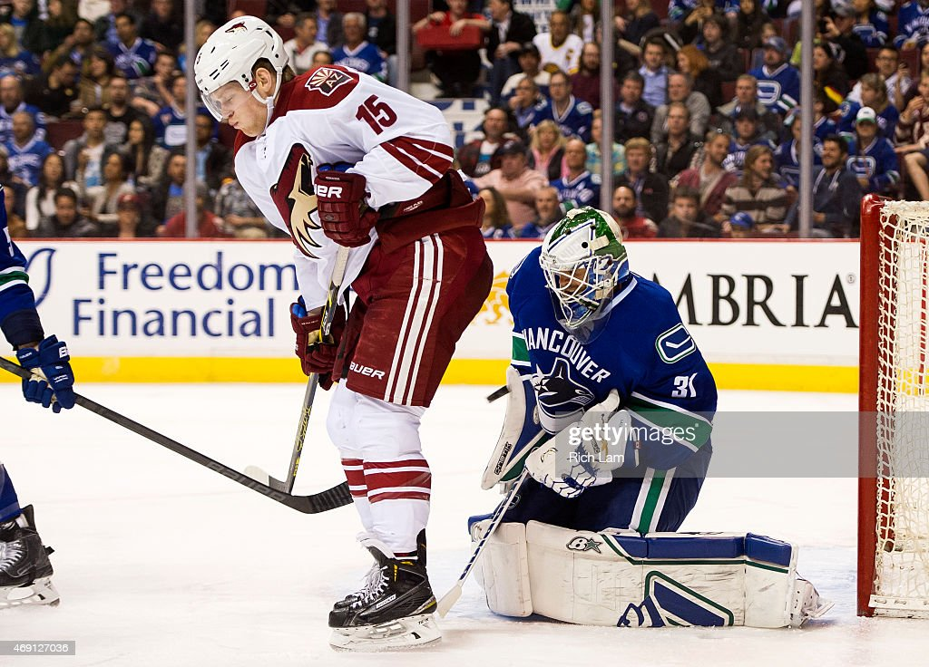 Goalie Eddie Lack #31 of the Vancouver Canucks makes a save while screened by Henrik Samuelsson #15 of the Arizona Coyotes in NHL action on April 9, 2015 at Rogers Arena in Vancouver, British Columbia, Canada.