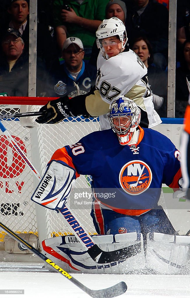 Goalie Evgeni Nabokov #20 of the New York Islanders watches the puck as Sidney Crosby #87 of the Pittsburgh Penguins follows it from behind in an NHL hockey game at Nassau Veterans Memorial Coliseum on March 22, 2013 in Uniondale, New York.
