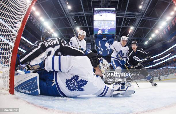 Goalie Frederik Andersen of the Toronto Maple Leafs looks for the puck while teammate Jake Gardiner battles JT Brown and Byron Froese of the Tampa...