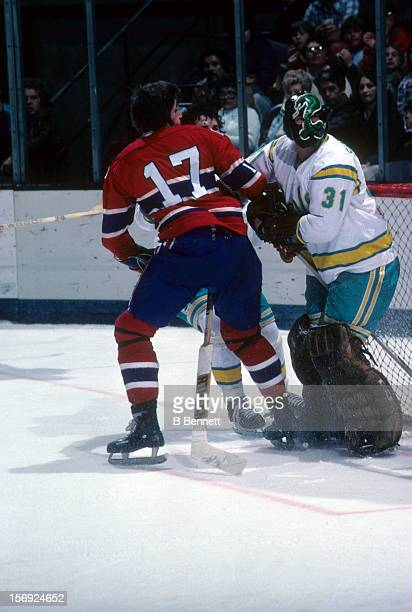 Goalie Gary 'Cobra' Simmons of the California Golden Seals tries to clear the front of the net as Murray Wilson of the Montreal Canadiens runs into...