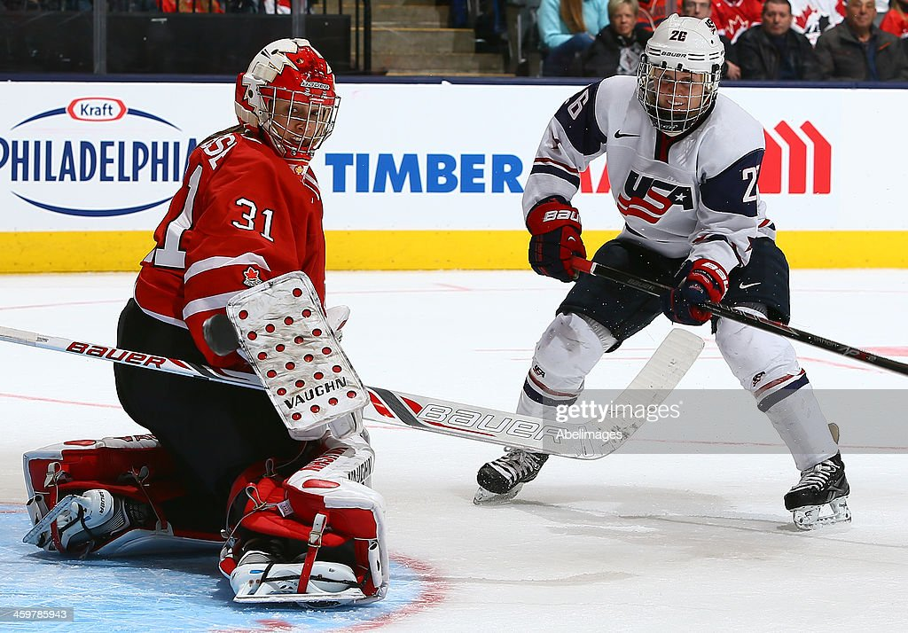 Goalie Genevieve Lacasse of Team Canada stops Kendall Coyne of Team USA during a Sochi Olympics preparation game at the Air Canada Centre December 30...