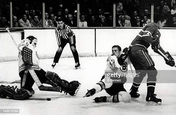 Goalie Gerry Cheever of the Boston Bruins makes the save as his teammate Don Awrey holds Jean Beliveau of the Montreal Canadiens during Game 5 of the...