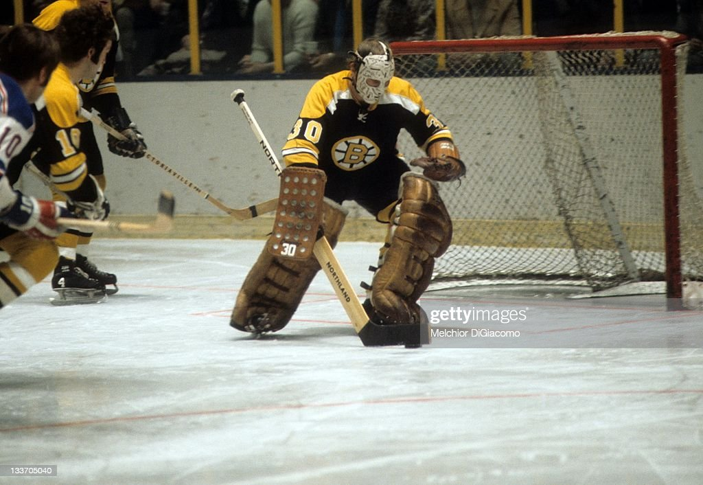 Goalie Gerry Cheevers of the Boston Bruins looks to pass the puck during an NHL game against the New York Rangers on February 2 1972 at the Madison...