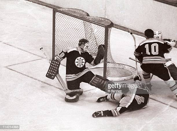 Goalie Gerry Cheevers of the Boston Bruins makes the save as his teammates Bobby Orr and Carol Vadnais defend during an NHL game circa 1972