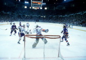 Goalie Grant Fuhr and Kevin Lowe of the Edmonton Oilers follow the puck in the air as Bryan Trottier and Clark Gillies of the New York Islanders look...