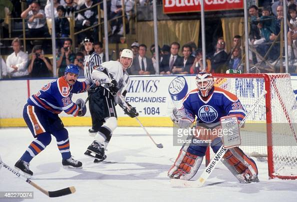 Goalie Grant Fuhr of the Edmonton Oilers defends the net as his teammate Charlie Huddy defends against Wayne Gretzky of the Los Angeles Kings on...