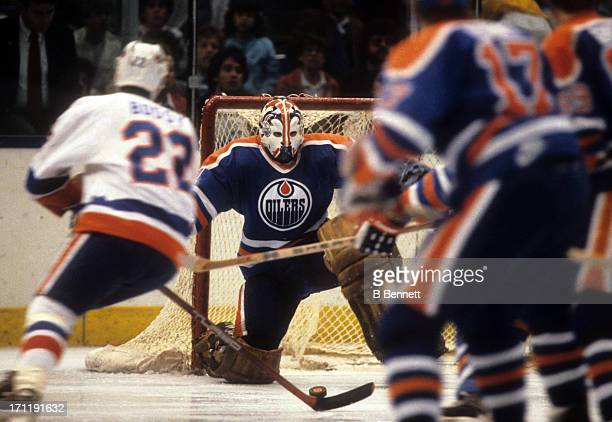 Goalie Grant Fuhr of the Edmonton Oilers defends the net as Mike Bossy of the New York Islanders looks to shoot during the 1984 Stanley Cup Finals in...