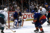 Goalie Grant Fuhr of the St Louis Blues defends the net as his teammates Marc Bergevin and Libor Zabransky defend against Teemu Selanne and Warren...