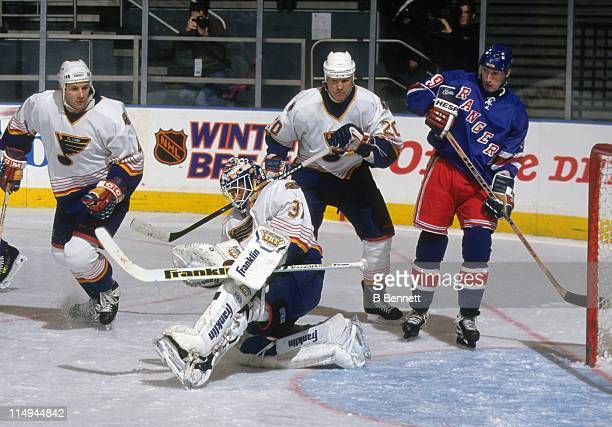 Goalie Grant Fuhr of the St Louis Blues makes the save as teammates Rudy Poeschek and Marc Bergevin defend against Wayne Gretzky of the New York...