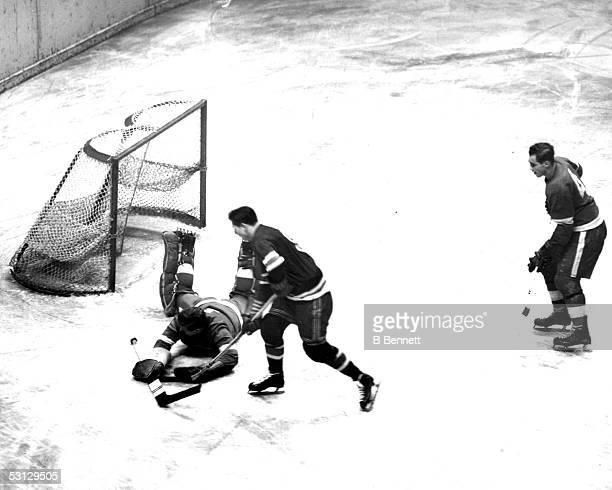 Goalie Harry Lumley of the Detroit Red Wings makes the diving save on Pentti Lund of the New York Rangers as defenseman Red Kelly of the Red Wings...