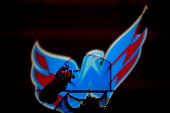 Goalie Henrik Lundqvist of the New York Rangers is illuminated by the Washington Capitals logo in Game Three of the Eastern Conference Semifinals...