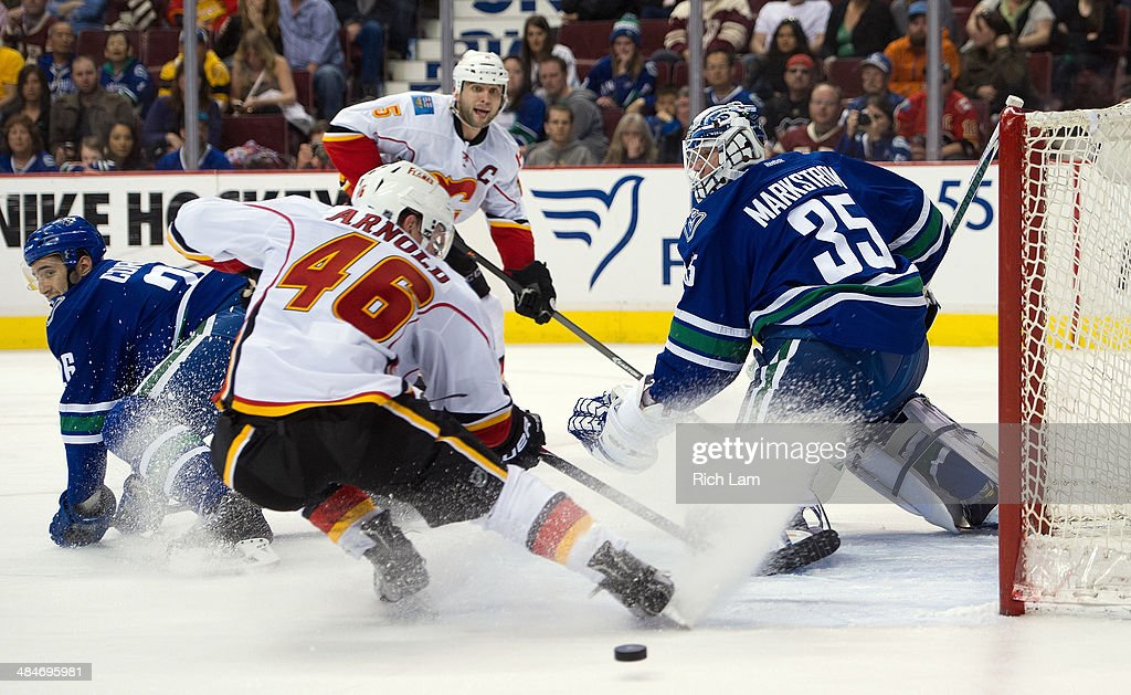 Goalie <a gi-track='captionPersonalityLinkClicked' href=/galleries/search?phrase=Jacob+Markstrom&family=editorial&specificpeople=5370948 ng-click='$event.stopPropagation()'>Jacob Markstrom</a> #35 of the Vancouver Canucks watches the pass from <a gi-track='captionPersonalityLinkClicked' href=/galleries/search?phrase=Mark+Giordano&family=editorial&specificpeople=696867 ng-click='$event.stopPropagation()'>Mark Giordano</a> #5 of the Calgary Flames get past Bill Arnold #46 of the Calgary Flames during the second period in NHL action on April 13, 2014 at Rogers Arena in Vancouver, British Columbia, Canada. <a gi-track='captionPersonalityLinkClicked' href=/galleries/search?phrase=Frank+Corrado&family=editorial&specificpeople=7364772 ng-click='$event.stopPropagation()'>Frank Corrado</a> #26 of the Vancouver Canucks tries to help defend on the play.