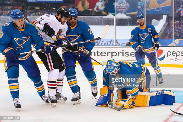 Goalie Jake Allen of the St Louis Blues covers the puck as Andrew Desjardins of the Chicago Blackhawks gets physical with Jori Lehtera and Ryan...
