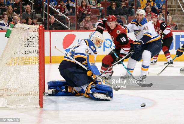 Goalie Jake Allen of the St Louis Blues makes a pad save on the puck as Christian Dvorak of the Arizona Coyotes and Robert Bortuzzo of the Blues...