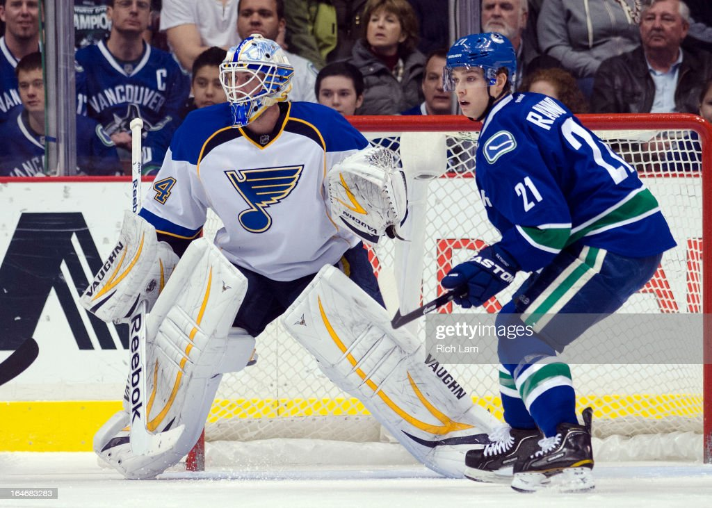 Goalie Jake Allen #34 of the St. Louis Blues readies to make a save while Mason Raymond #21 of the Vancouver Canucks stands in front of the net during NHL action on March 19, 2013 at Rogers Arena in Vancouver, British Columbia, Canada.