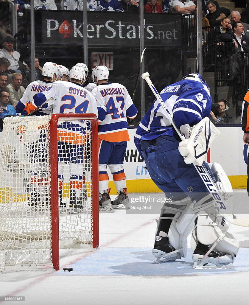 Goalie James Reimer #34 of the Toronto Maple Leafs looks for the puck as John Tavares of the New York Islanders celebrates a first-period goal with teammates during NHL game action April 18, 2013 at the Air Canada Centre in Toronto, Ontario, Canada.