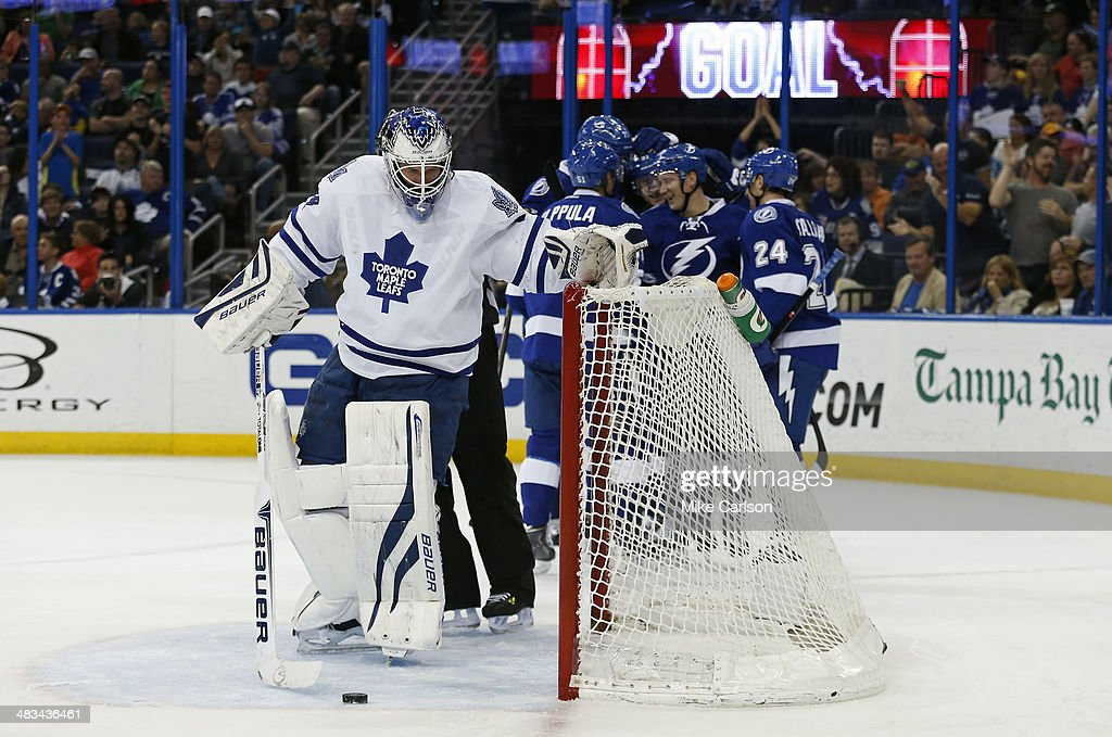 Goalie James Reimer #34 of the Toronto Maple Leafs retrieves the puck from the net as members of the Tampa Bay Lightning celebrate a goal at the Tampa Bay Times Forum on April 8, 2014 in Tampa, Florida.