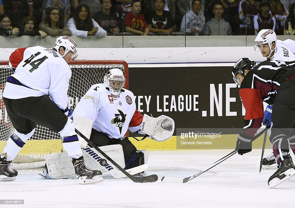 Goalie Jean-Philippe Lamoureux of Villach SV makes a save against Taylor Paytt (R, black shirt) of Geneve-Servette next to Geoff Waugh (L) and Stefan Bacher of Villach SV during the Champions Hockey League group stage game between Geneve-Servette and Villach SV on August 23, 2014 in Geneva, Switzerland.