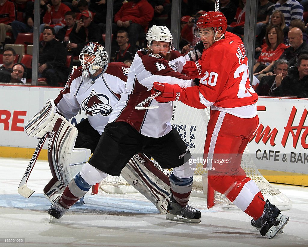 Goalie Jean-Sebastien Giguere #35 of the Colorado Avalanche looks around teamate Greg Zanon #4 as he battles with Drew Miller #20 of the Detroit Red Wings on the side of the net during a NHL game at Joe Louis Arena on April 1, 2013 in Detroit, Michigan.
