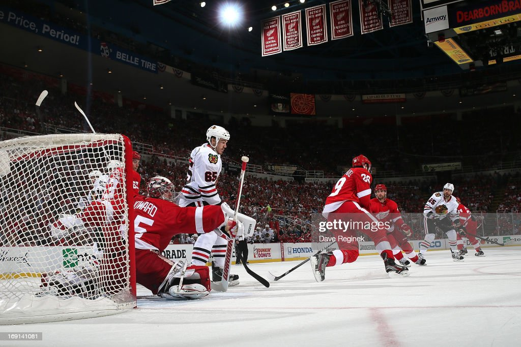 Goalie <a gi-track='captionPersonalityLinkClicked' href=/galleries/search?phrase=Jimmy+Howard&family=editorial&specificpeople=2118637 ng-click='$event.stopPropagation()'>Jimmy Howard</a> #30 and <a gi-track='captionPersonalityLinkClicked' href=/galleries/search?phrase=Carlo+Colaiacovo&family=editorial&specificpeople=234960 ng-click='$event.stopPropagation()'>Carlo Colaiacovo</a> #28 of the Detroit Red Wings both get in the way of a shot as Andrew Shaw #65 of the Chicago Blackhawks positions himself in front of the net during Game Three of the Western Conference Semifinals during the 2013 NHL Stanley Cup Playoffs at Joe Louis Arena on May 20, 2013 in Detroit, Michigan.