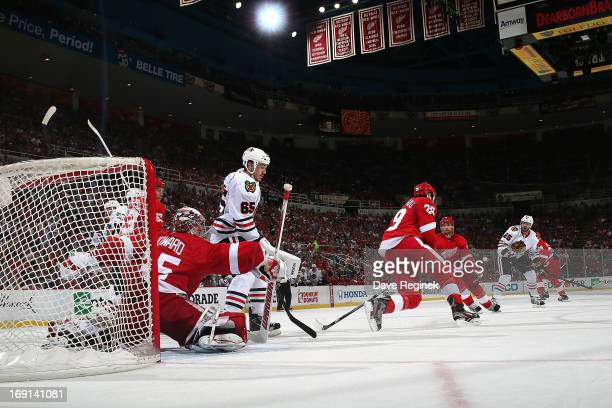 Goalie Jimmy Howard and Carlo Colaiacovo of the Detroit Red Wings both get in the way of a shot as Andrew Shaw of the Chicago Blackhawks positions...