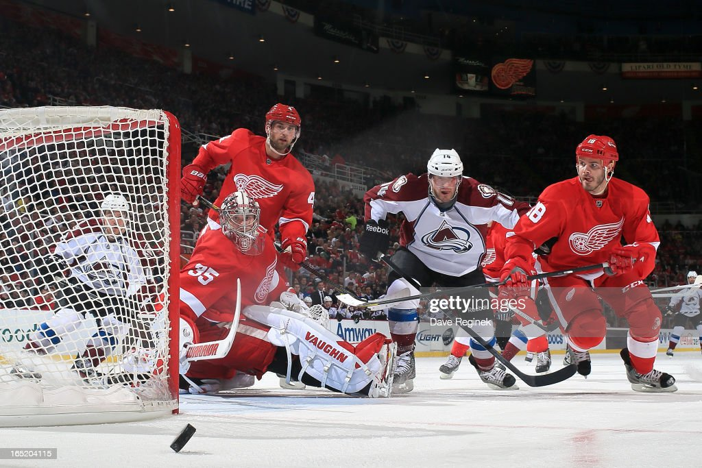 Goalie <a gi-track='captionPersonalityLinkClicked' href=/galleries/search?phrase=Jimmy+Howard&family=editorial&specificpeople=2118637 ng-click='$event.stopPropagation()'>Jimmy Howard</a> #35 and <a gi-track='captionPersonalityLinkClicked' href=/galleries/search?phrase=Jakub+Kindl&family=editorial&specificpeople=716743 ng-click='$event.stopPropagation()'>Jakub Kindl</a> #4 of the Detroit Red Wings watch the puck go to the side of the net as teamate <a gi-track='captionPersonalityLinkClicked' href=/galleries/search?phrase=Ian+White&family=editorial&specificpeople=581742 ng-click='$event.stopPropagation()'>Ian White</a> #18 races David Van Der Gulk #14 of the Colorado Avalanche to it during a NHL game at Joe Louis Arena on April 1, 2013 in Detroit, Michigan.