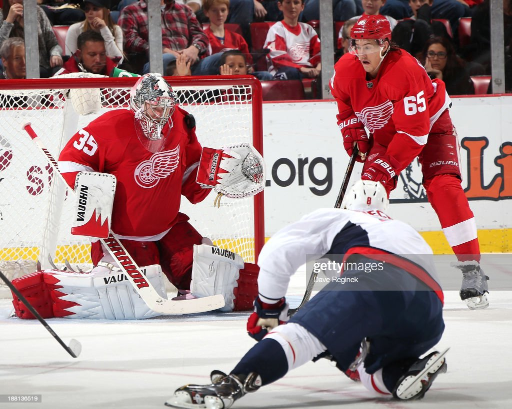 Goalie <a gi-track='captionPersonalityLinkClicked' href=/galleries/search?phrase=Jimmy+Howard&family=editorial&specificpeople=2118637 ng-click='$event.stopPropagation()'>Jimmy Howard</a> #35 makes a save on a shot by Alex Ovechkin #8 of the Washington Capitals as Danny DeKeyser #65 of the Red Wings looks on during an NHL game at Joe Louis Arena on November 15, 2013 in Detroit, Michigan.