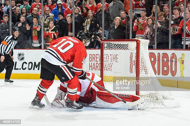 Goalie Jimmy Howard of the Detroit Red Wings blocks the shootout shot by Patrick Sharp of the Chicago Blackhawks to win the game 32 during the NHL...