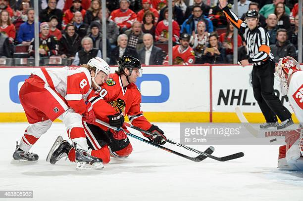 Goalie Jimmy Howard of the Detroit Red Wings blocks the shot taken by Brandon Saad of the Chicago Blackhawks as Justin Abdelkader reaches from behind...