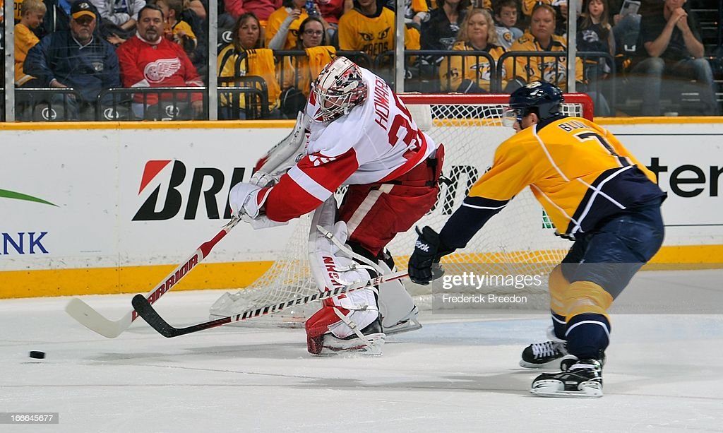 Goalie Jimmy Howard #35 of the Detroit Red Wings dumps the puck out of reach of Jonathon Blum #7 of the Nashville Predators at the Bridgestone Arena on April 14, 2013 in Nashville, Tennessee.