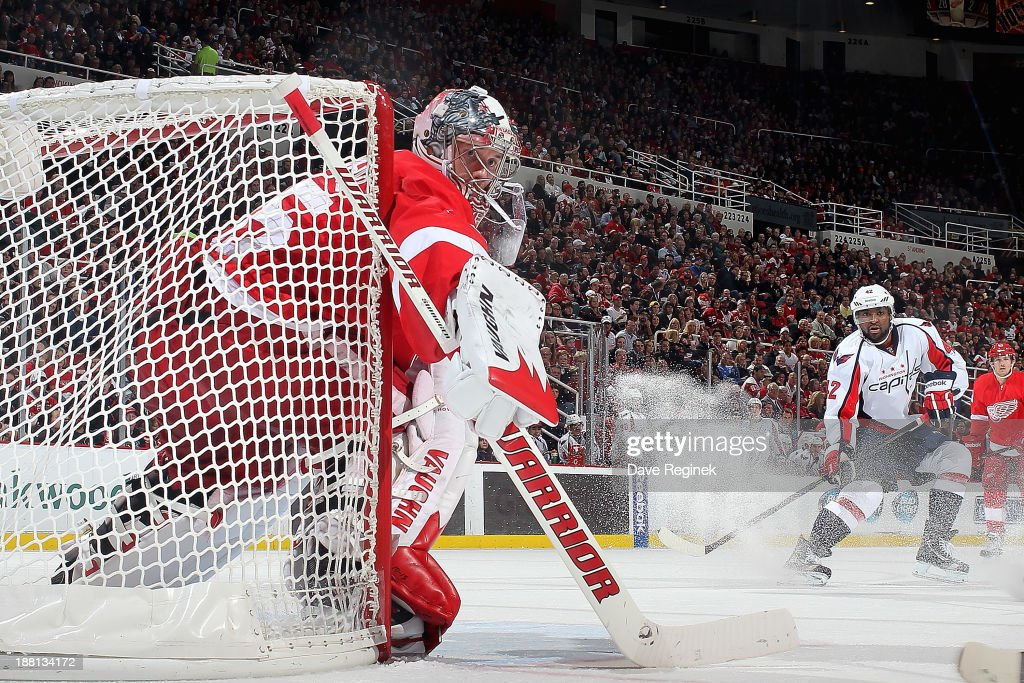 Goalie <a gi-track='captionPersonalityLinkClicked' href=/galleries/search?phrase=Jimmy+Howard&family=editorial&specificpeople=2118637 ng-click='$event.stopPropagation()'>Jimmy Howard</a> #35 of the Detroit Red Wings hugs the post as Joel Ward #42 of the Washington Capitals skates to the front of the net during an NHL game at Joe Louis Arena on November 15, 2013 in Detroit, Michigan.