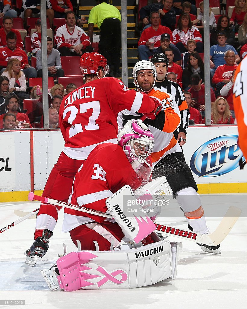 Goalie Jimmy Howard #35 of the Detroit Red Wings makes a save as teammate Kyle Quincey #27 ties up Maxime Talbot #25 of the Philadelphia Flyers to the side of him during a NHL game at Joe Louis Arena on October 12, 2013 in Detroit, Michigan.