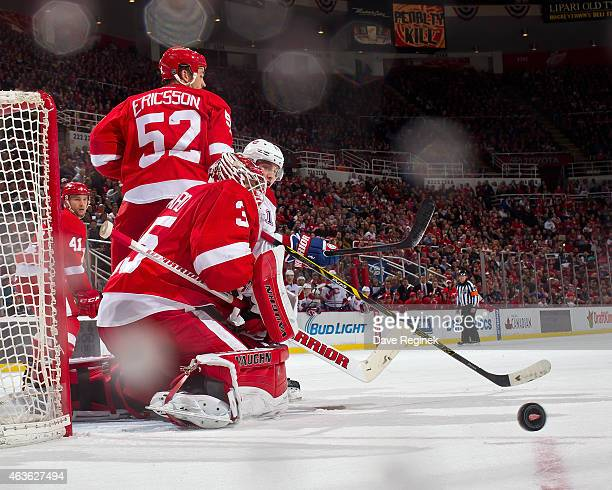 Goalie Jimmy Howard of the Detroit Red Wings makes a save as teammate Jonathan Ericsson defends Brendan Gallagher of the Montreal Canadiens in front...