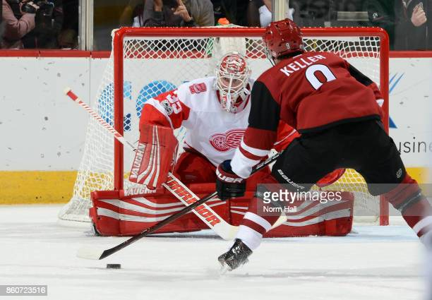 Goalie Jimmy Howard of the Detroit Red Wings positions himself to make a save as Clayton Keller of the Arizona Coyotes skates in with the puck during...