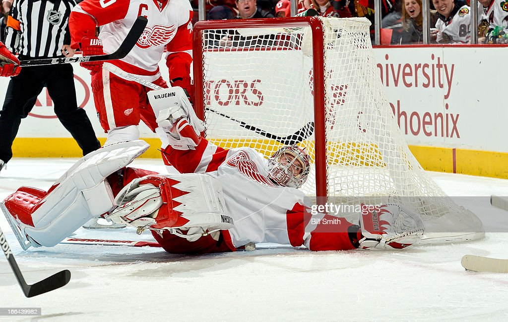 Goalie Jimmy Howard #35 of the Detroit Red Wings stretches out to block the puck against the Chicago Blackhawks during the NHL game on April 12, 2013 at the United Center in Chicago, Illinois.