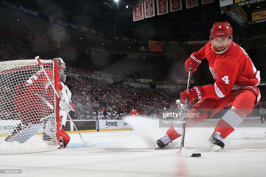 Goalie <a gi-track='captionPersonalityLinkClicked' href=/galleries/search?phrase=Jimmy+Howard&family=editorial&specificpeople=2118637 ng-click='$event.stopPropagation()'>Jimmy Howard</a> #35 of the Detroit Red Wings watches as teamate <a gi-track='captionPersonalityLinkClicked' href=/galleries/search?phrase=Jakub+Kindl&family=editorial&specificpeople=716743 ng-click='$event.stopPropagation()'>Jakub Kindl</a> #4 circles away from the net with the puck during a NHL game against the Colorado Avalanche at Joe Louis Arena on April 1, 2013 in Detroit, Michigan.