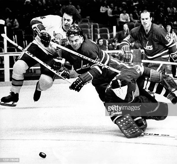 Goalie Joe Daley of the Winnipeg Jets tries to clear the puck as he collides with teammate Joe Zanussi and Mike Walton of the Minnesota Fighting...