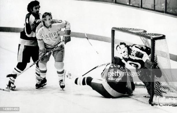 Goalie Joe Junkin of the New York Golden Blades is knocked into his net by teammate Ken Block as Kevin Morrison of the Blades defends Johnny McKenzie...