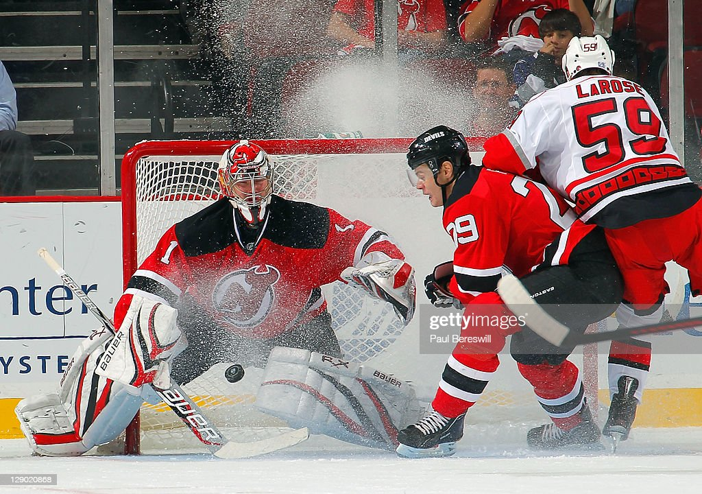 Goalie Johan Hedberg #1 of the New Jersey Devils stops a shot by Chad LaRose #59 of the Carolina Hurricanes during the second period of an NHL hockey game as Mark Fayne #29 of the Devils helps defend at the Prudential Center on October 10, 2011 in Newark, New Jersey.