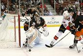 Goalie John Gibson of the Anaheim Ducks knocks the puck away from Erik Condra of the Ottawa Senators at Honda Center on February 25 2015 in Anaheim...