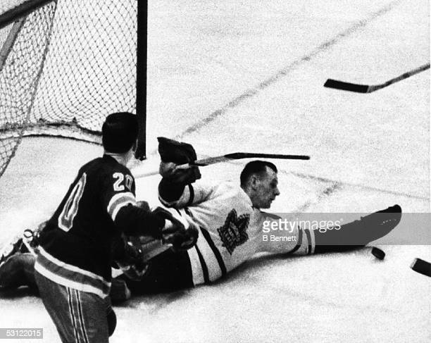 Goalie Johnny Bower looks to make the save but Reggie Fleming of the New York Rangers pops it in the air to score the Ranger's second goal on...
