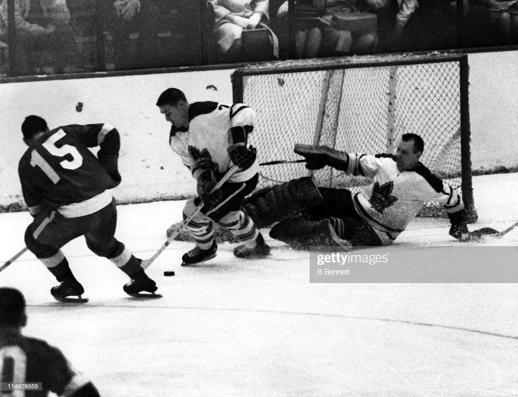Goalie <a gi-track='captionPersonalityLinkClicked' href=/galleries/search?phrase=Johnny+Bower&family=editorial&specificpeople=239053 ng-click='$event.stopPropagation()'>Johnny Bower</a> #1 of the Toronto Maple Leafs blocks the net as his teammate Tim Horton #7 skates with the puck while being defended by Andre Pronovost #15 of the Detroit Red Wings circa 1963 at the Detroit Olympia Stadium in Detroit, Michigan.