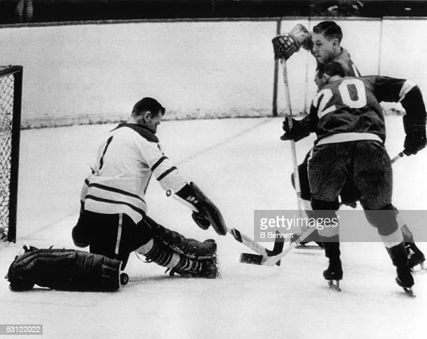 Goalie Johnny Bower of the Toronto Maple Leafs blocks the shot by Parker MacDonald of the Detroit Red Wings as his teammate Alex Delvecchio looks for...