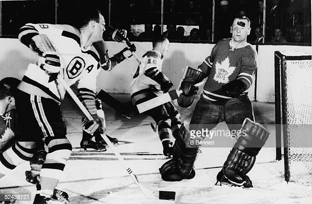 Goalie Johnny Bower of the Toronto Maple Leafs keeps his eyes on an airborne puck shot by Doug Mohns of the Boston Bruins during their game at Maple...