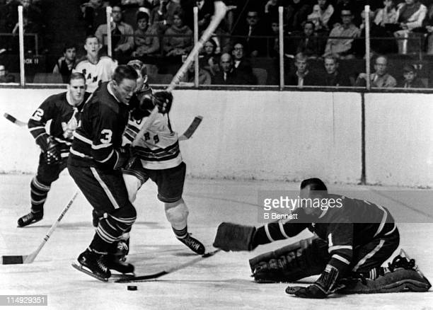 Goalie Johnny Bower of the Toronto Maple Leafs looks to cover the puck as his teammate Marcel Pronovost blocks out Orland Kurtenbach of the New York...