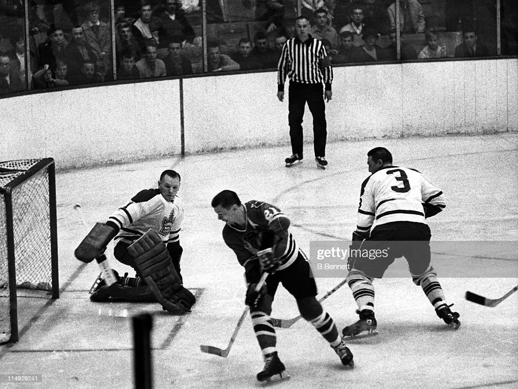 Goalie <a gi-track='captionPersonalityLinkClicked' href=/galleries/search?phrase=Johnny+Bower&family=editorial&specificpeople=239053 ng-click='$event.stopPropagation()'>Johnny Bower</a> #1 of the Toronto Maple Leafs looks to make the save against Stan Mikita #21 of the Chicago Blackhawks as Bower's teammate <a gi-track='captionPersonalityLinkClicked' href=/galleries/search?phrase=Marcel+Pronovost&family=editorial&specificpeople=5361202 ng-click='$event.stopPropagation()'>Marcel Pronovost</a> #3 plays defense on January 29, 1967 at the Chicago Stadium in Chicago, Illinois.